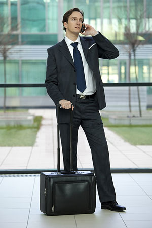 executive traveler with travel bag, making a cell phone call